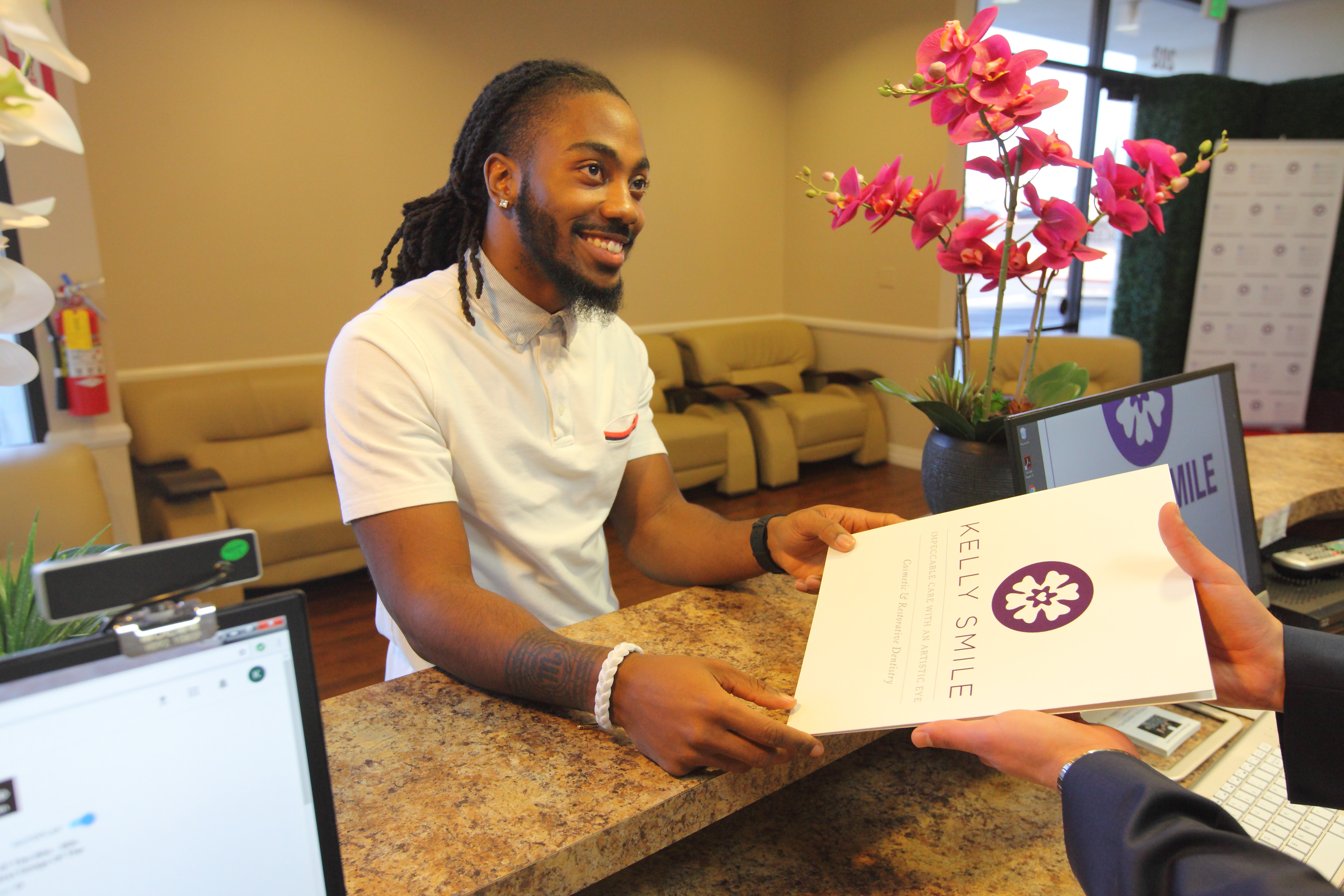 a patient handing in new patient forms at Kelly Smile Dentistry