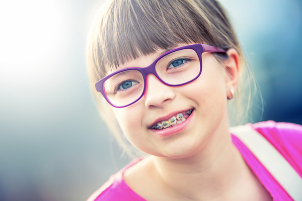 Young girl with glasses wearing braces